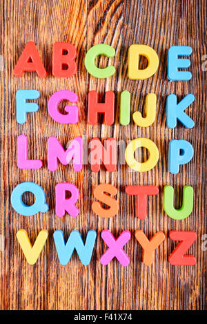 composition of colorful plastic alphabet letters on wooden background - Stock Photo