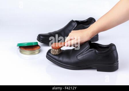 woman's hand polishing black leather shoes with shoe brush on white background - Stock Photo