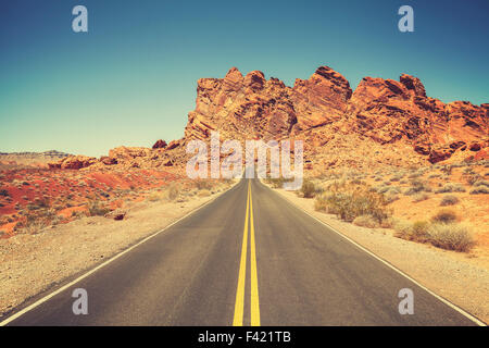 Retro stylized road through rocky desert in Valley of Fire State Park, Nevada. - Stock Photo
