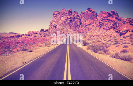 Vintage retro stylized road through rocky desert in Valley of Fire State Park, Nevada. - Stock Photo