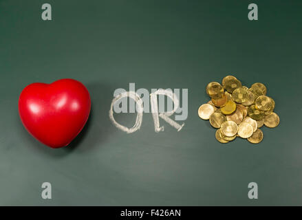 Red foam heart and pile of shiny golden coins on green board, conceptual image about the choice between soul or - Stock Photo