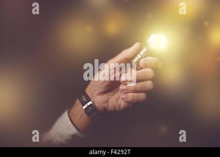 Big business idea visual metaphor, businessman with light bulb lightning up the dark office interior, retro toned - Stock Photo