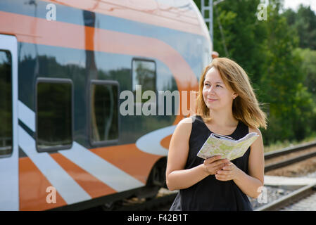 Girl holding map and watching on a train - Stock Photo