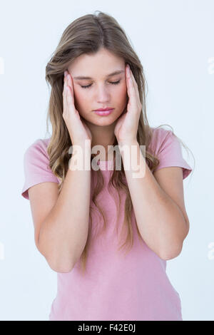 Pretty woman with headache hands on temples - Stock Photo