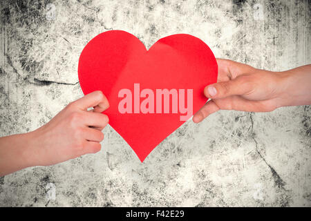 Composite image of hands holding red heart - Stock Photo
