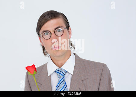 Geeky businessman offering a rose - Stock Photo