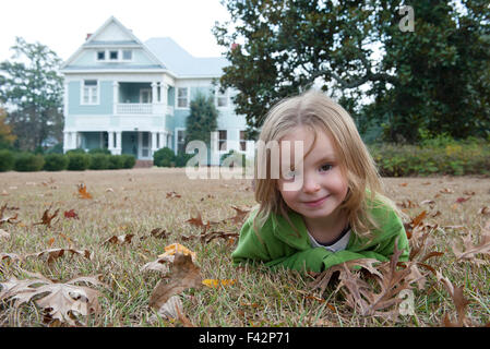 Girl lying on stomach on lawn, smiling, portrait - Stock Photo