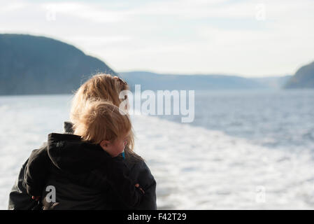 Mother and young son looking at tranquil lake view - Stock Photo