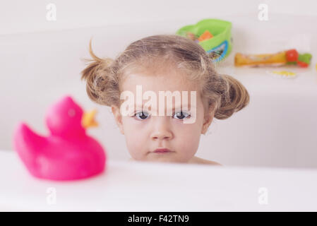 Little girl sitting in bath with unhappy expression, portrait - Stock Photo