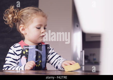 Little girl wiping table with spong - Stock Photo