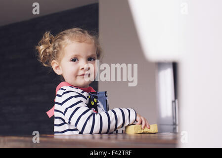 Little girl helping with housework, portrait - Stock Photo