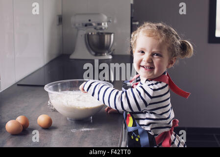 Little girl mixing batter, smiling, portrait - Stock Photo