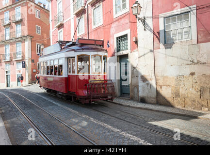LISBON, PORTUGAL - SEPTEMBER 26: Unidentified people sitting in the red tram  goes by the street of Lisbon city center on Septem