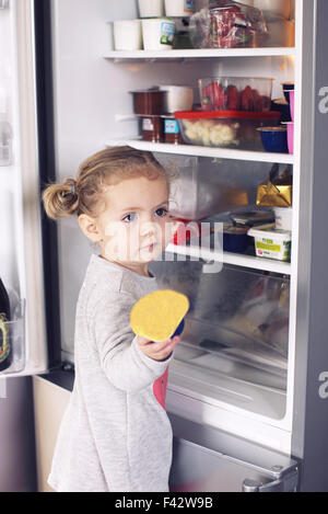 Little girl taking food out of refrigerator - Stock Photo