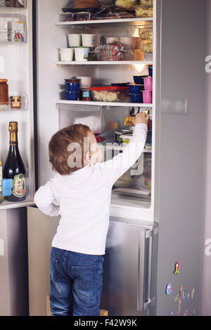 Little boy reaching for something in refrigerator - Stock Photo