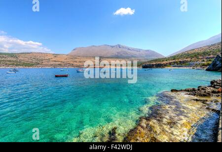 The beautiful Greek coastline with crystal clear waters and many boats anchored near Diros caves in Greece. A stunning - Stock Photo