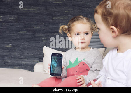 Little girl showing smartphone to her brother - Stock Photo