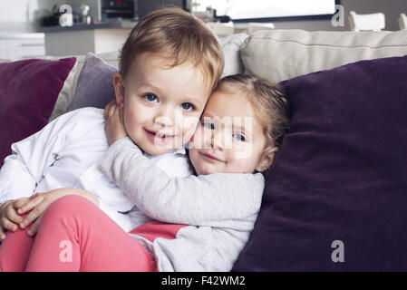 Young siblings embracing, portrait - Stock Photo