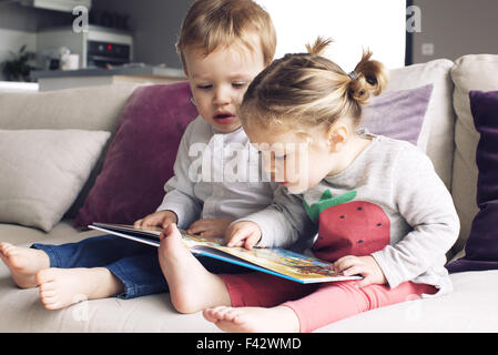 Young siblings looking at book together - Stock Photo