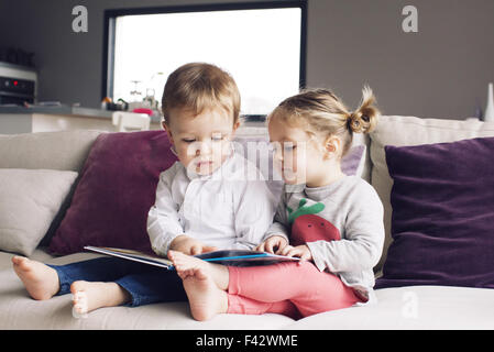 Young siblings looking at book together on sofa - Stock Photo