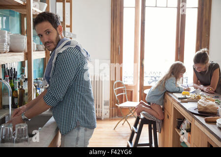 Family in kitchen, man doing dishes in foreground - Stock Photo