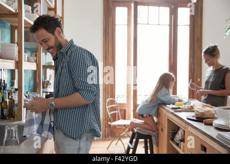 Family in kitchen, man drying dishes in foreground - Stock Photo