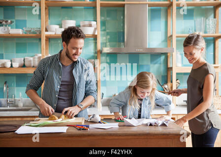Young daughter drawing at kitchen counter while parents prepare meal - Stock Photo