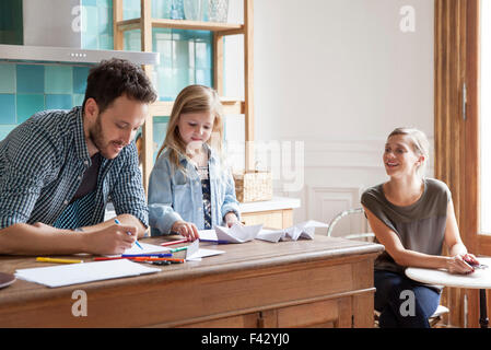 Parents spending time with young daughter at home - Stock Photo