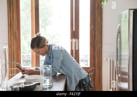 Young woman using smartphone in kitchen - Stock Photo