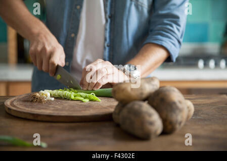 Man cutting spring onion in kitchen - Stock Photo