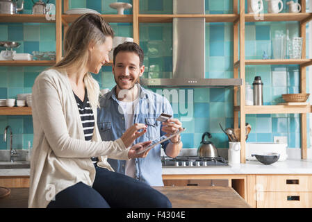 Couple using digital tablet in kitchen - Stock Photo
