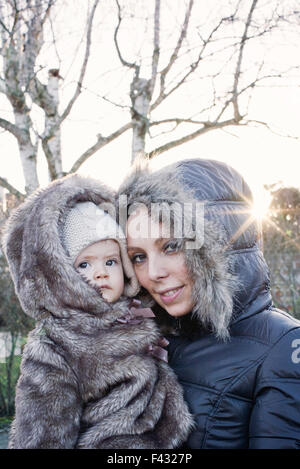 Mother holding baby girl outdoors, both wearing winter coats, portrait - Stock Photo