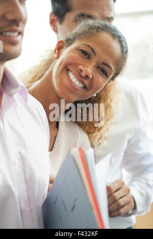 Businesswoman leaning out between two colleagues, smiling cheerfully - Stock Photo