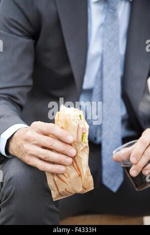Businessman holding sandwich, cropped - Stock Photo