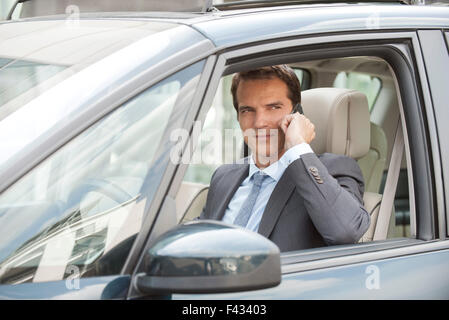 Businessman using cell phone while driving car - Stock Photo