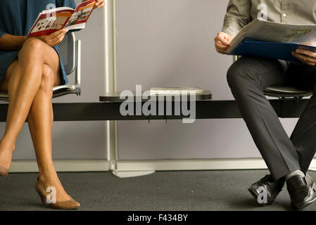 Man and woman sitting in waiting room, low section - Stock Photo