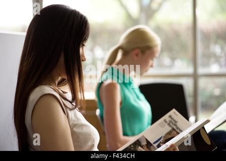 Woman reading magazine in waiting room - Stock Photo
