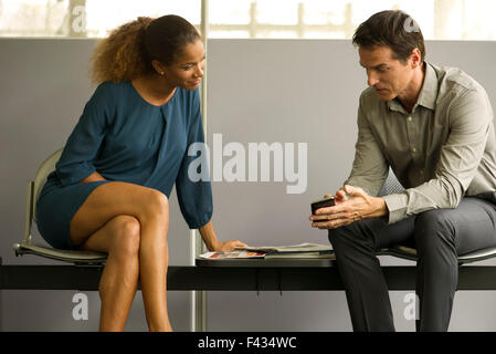 Professionals chatting in waiting room, man showing woman smartphone - Stock Photo