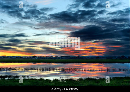 Spectacle clouds Sunset Reflection - Stock Photo