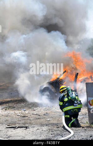 Firefighters extinguish a burning car - Stock Photo