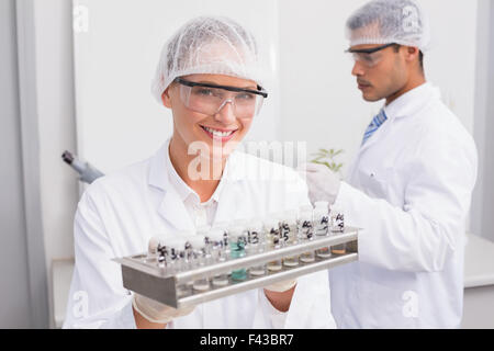 Happy scientists holding tubes - Stock Photo