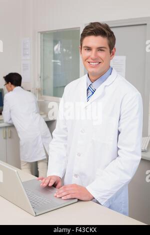 Smiling scientist using laptop - Stock Photo
