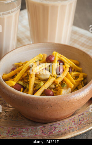 A bowl of spicy Bombay Mix served with Indian Masala chai tea - Stock Photo