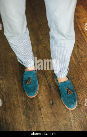 Close up of the legs and feet of a staff member at a city restaurant. - Stock Photo