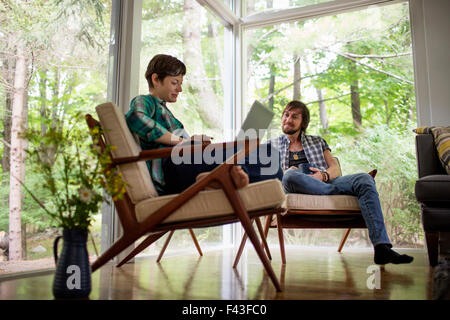 A man and woman sitting together in a room with large picture windows, one using a laptop. - Stock Photo