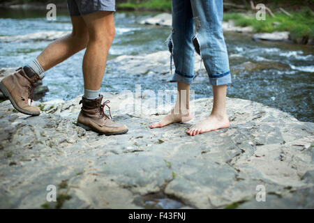 Two people on the rocks by a rushing river, man and woman, lower legs and feet. - Stock Photo