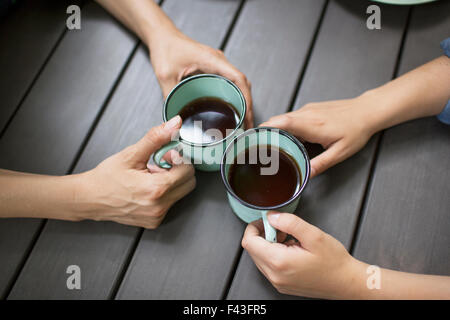 Two people seated at a table, drinking coffee, viewed from above. - Stock Photo