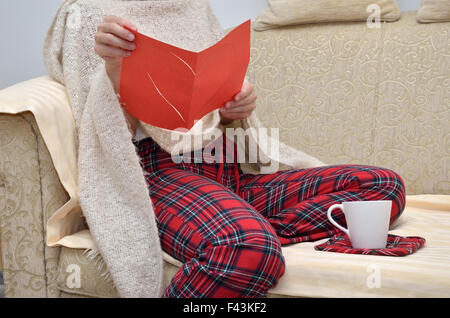 Lady in cozy home wear sitting on sofa and reading a love letter - Stock Photo