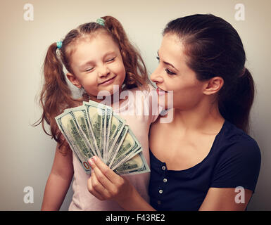Smiling mother looking on happy daughter holding cash of dollars. Vintage closeup portrait - Stock Photo