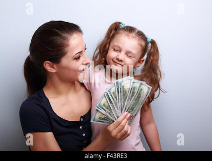 Smiling mother looking on happy daughter holding cash of dollars. Happy winning family. - Stock Photo